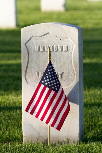 A grave site for an unidentified person with a flag in front of it at Fort Logan National Cemetery.
