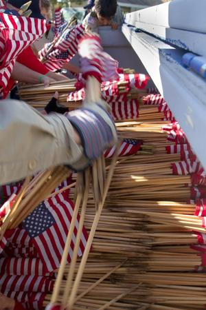 People reach into a container with 10,000 flags in it. Several of these containers were placed around Fort Logan Cemetery for the volunteers to pull from.