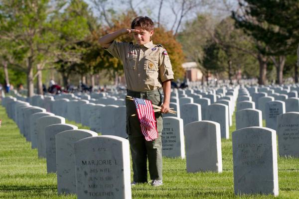 A boy scout salutes after planting a flag at the site of a grave marker at Fort Logan National Cemetery, May 25, 2013.