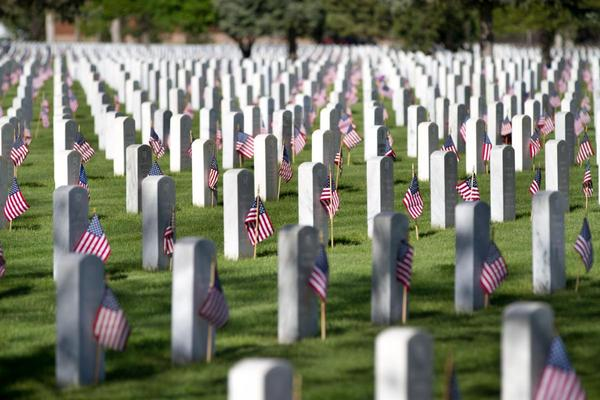 Flags wave in the breeze after being placed in from of the grave markers at Fort Logan National Cemetery, May 25, 2013.