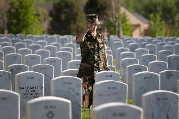 A member of the Young Marines salutes after placing the flag at a grave stone at Fort Logan National Cemeter, May 25, 2013.